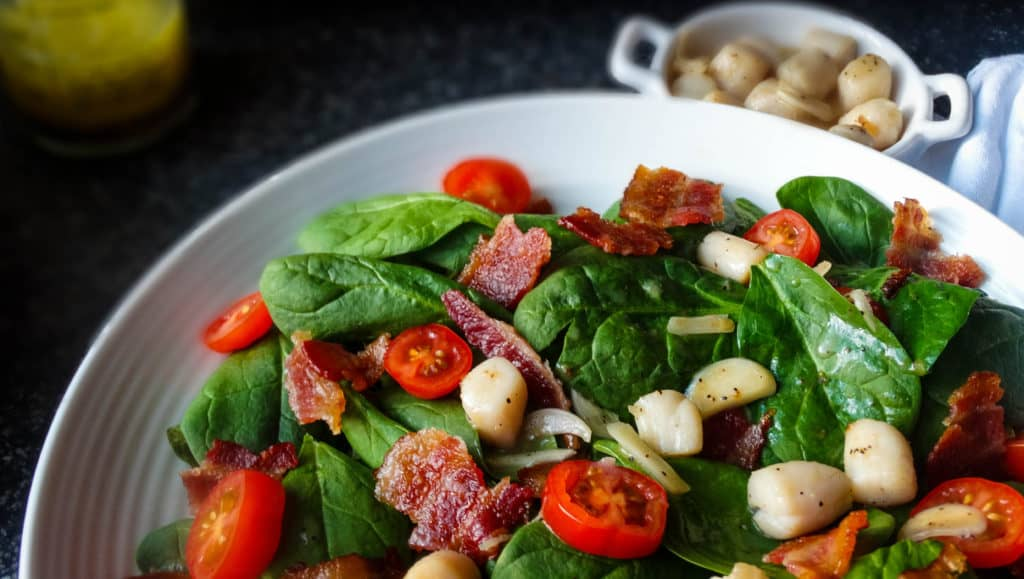 "alt=""bacon scallop salad in a white bowl with tomatoes and spinach and tossed with a garlic butter sauce"""
