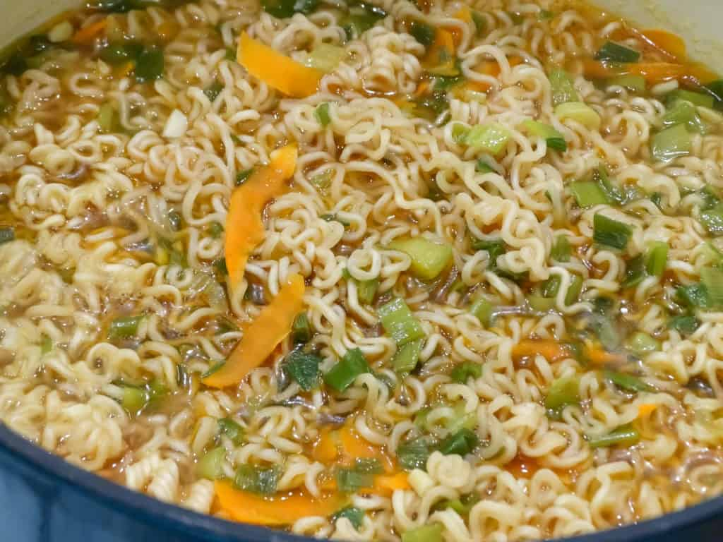 """alt=""""ramen noodles, carrots, scallions, chicken and beef broth, garlic, and soy sauce simmering in a blue dutch oven"""""""