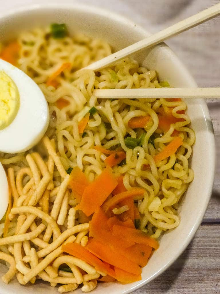 """alt=""""easy homemade ramen noodles topped with chow mein, carrots, and hard boiled sliced eggs in a white bowl with chopsticks"""""""