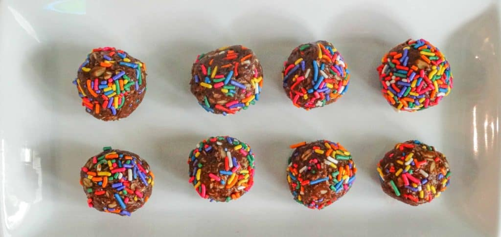 "alt=""healthy snacks for kids, double chocolate energy balls covered in rainbow sprinkled in two rows on a white serving plate"""
