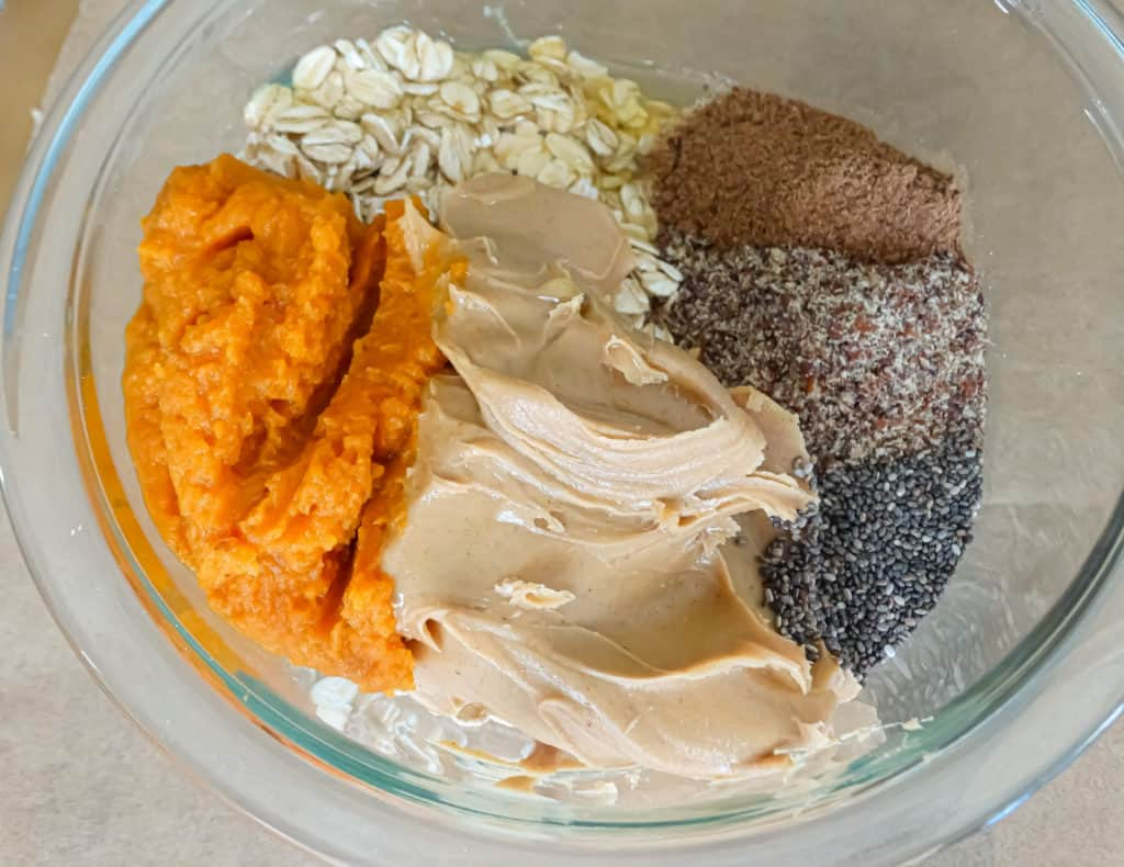 """alt=""""pumpkin, oats, peanut butter, chia seeds, honey, and ground flax in a clear mixing bowl"""""""