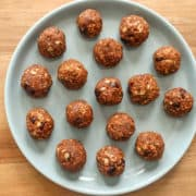 pumpkin spice energy balls spread on a grey plate with a brown background