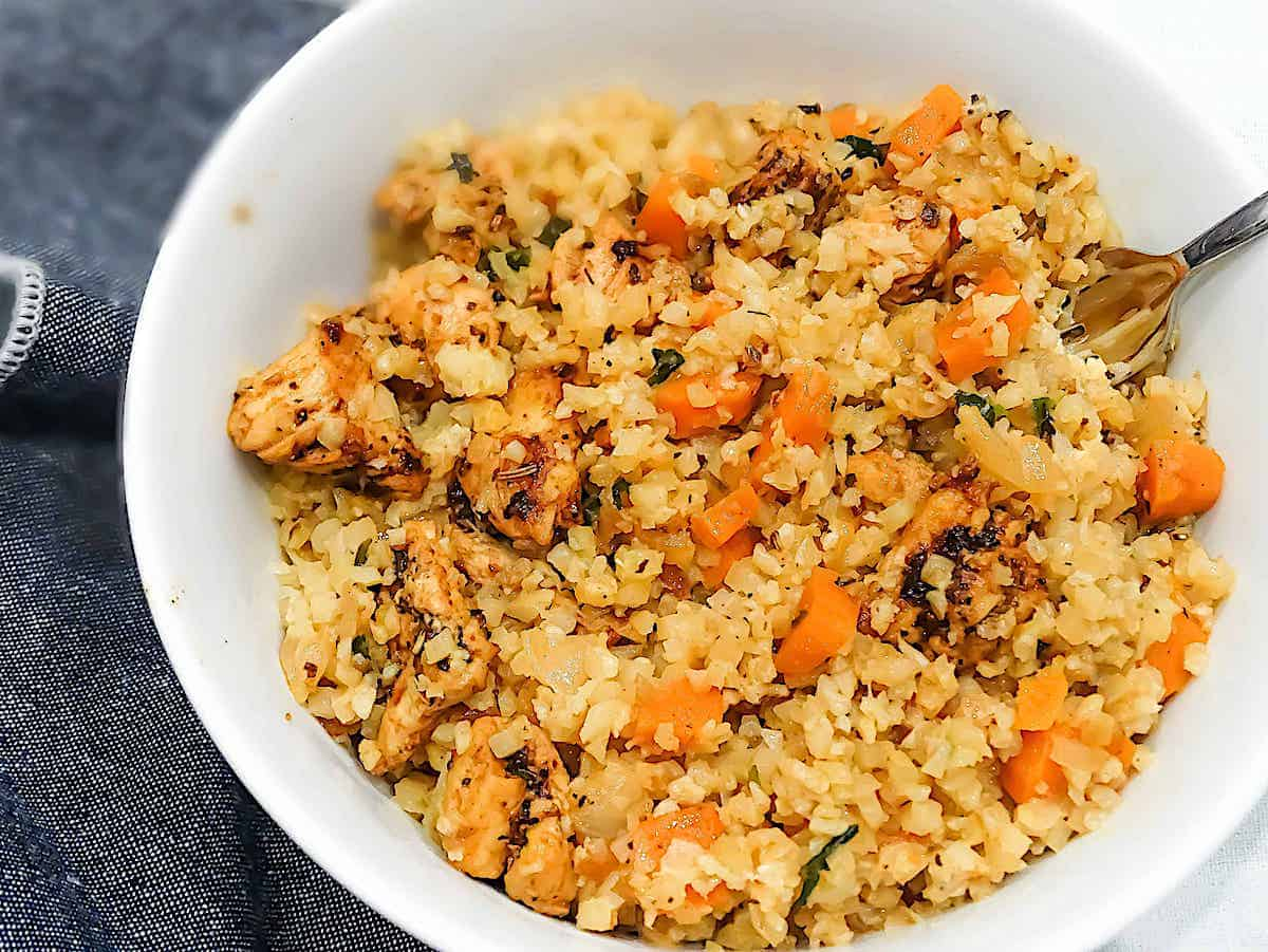 cauliflower rice stir fry with garlic butter chicken, carrots, and parsley in a white bowl