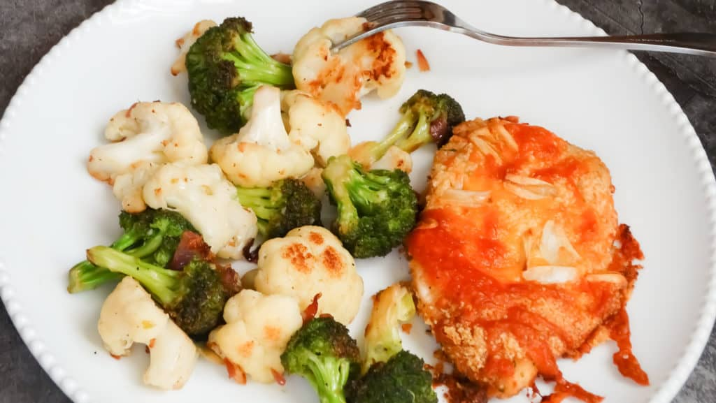 """alt=""""garlic cheddar chicken with roasted cauliflower and broccoli on a white serving plate"""""""