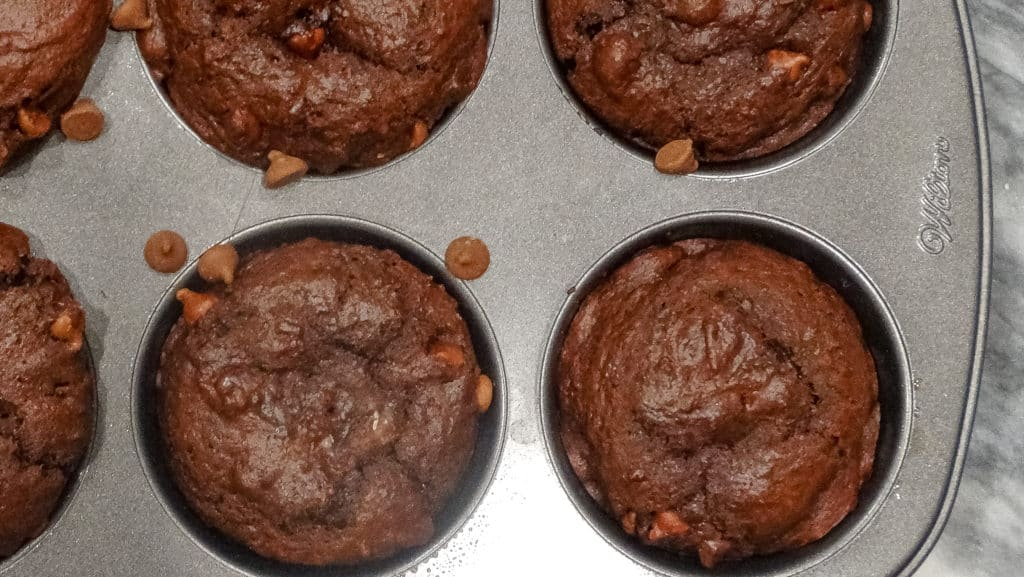 """alt=""""double chocolate bakery style muffins with chocolate chips in a jumbo muffin tin on a white marble cutting board"""""""