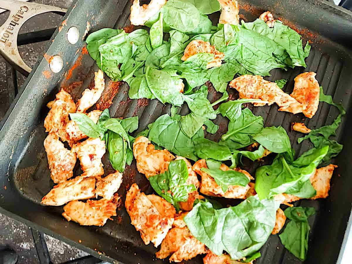 chicken and spinach frying in a griddle
