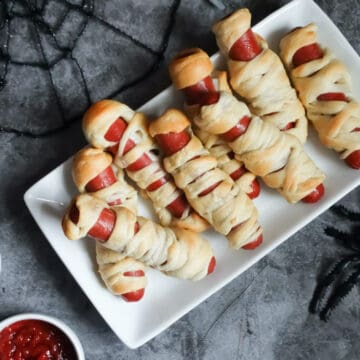 mummy wrapped hot dogs on a white plate