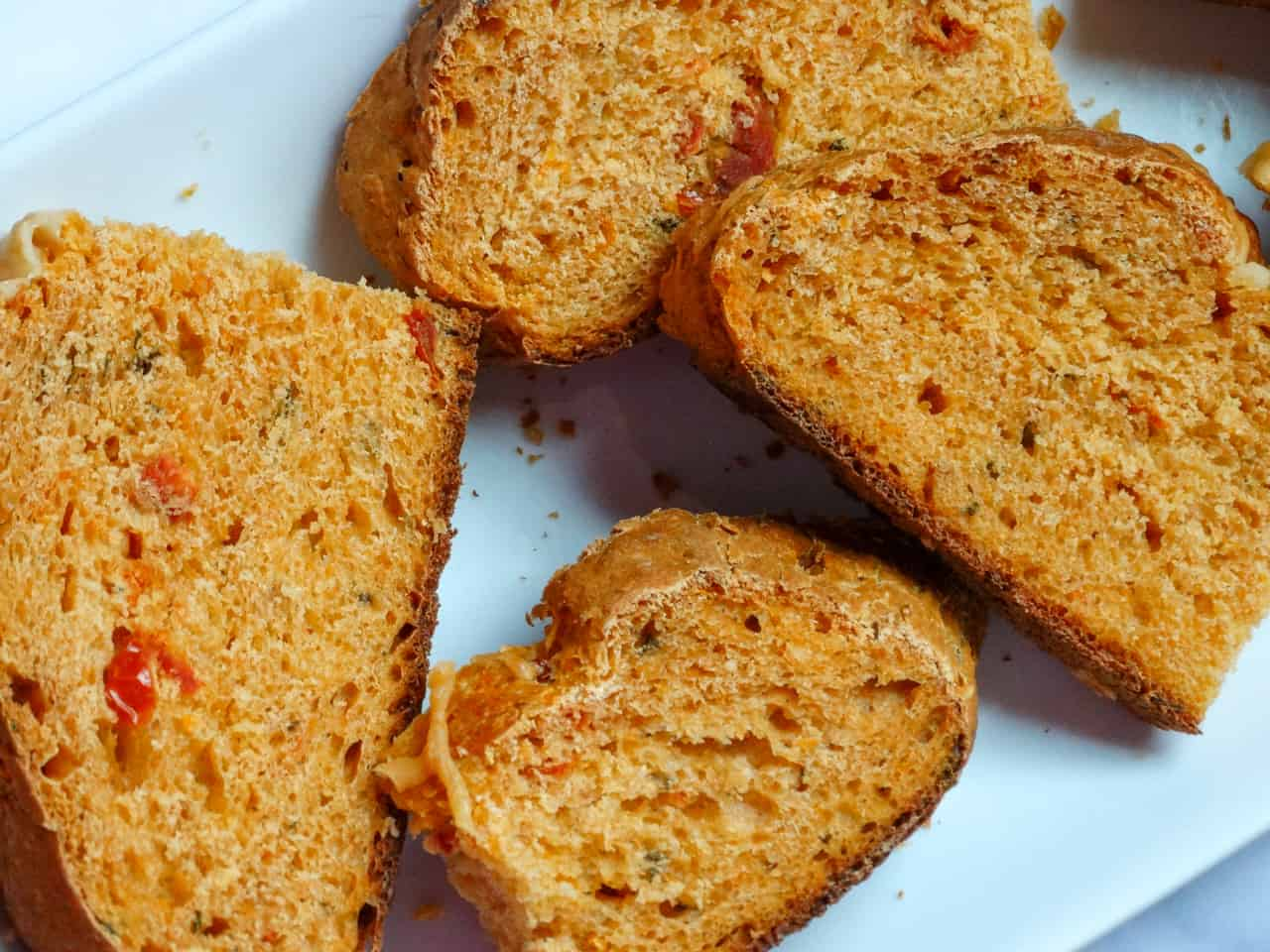 sun dried tomato basil bread made by hand sliced and on a white plate