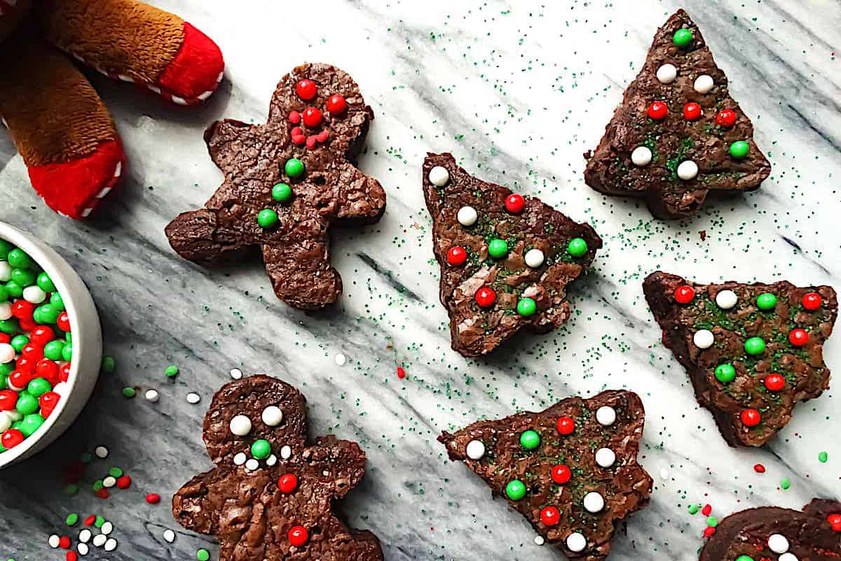 Christmas tree brownies decorated with sprinkles on a marble cutting board