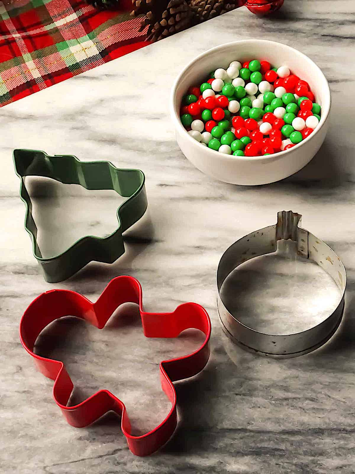 Christmas cookie cutters and sprinkles on a marble cutting board