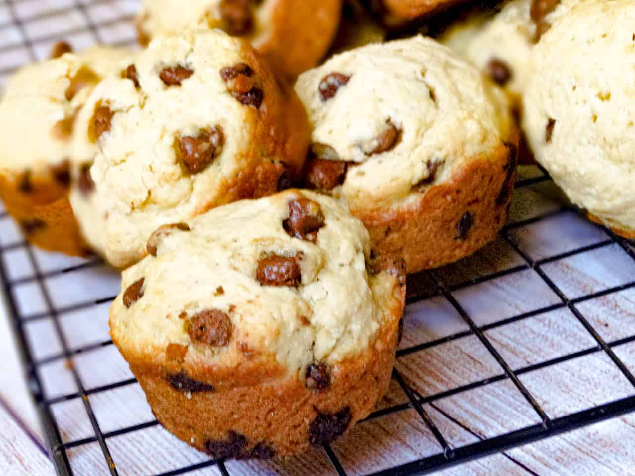 almond milk chocolate chip muffins in a pile on a cooling rack