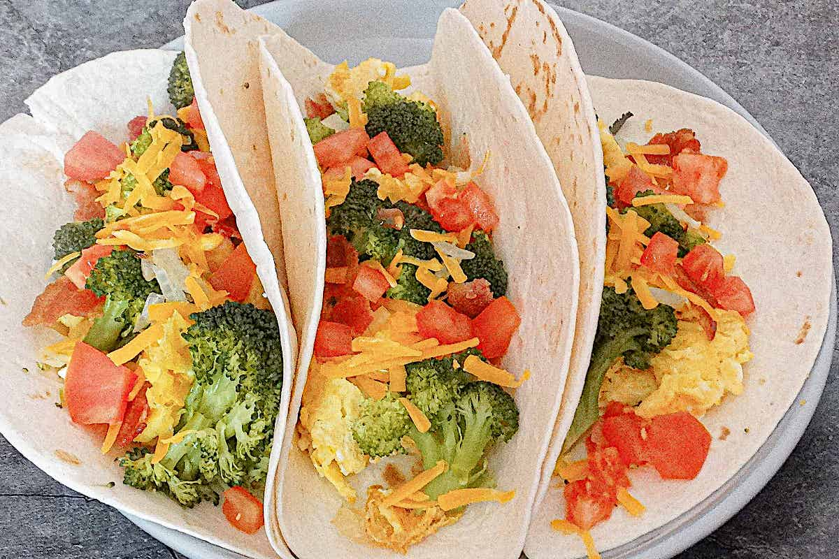 close up of broccoli egg and cheese breakfast burritos with cheddar cheese