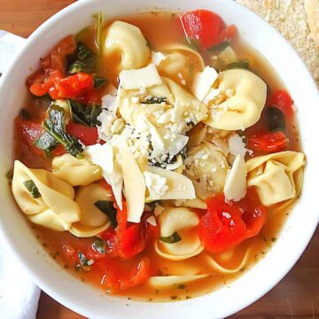 spinach tortellini soup in a white bowl