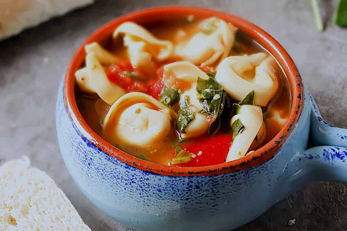 spinach tortellini soup in a blue cup