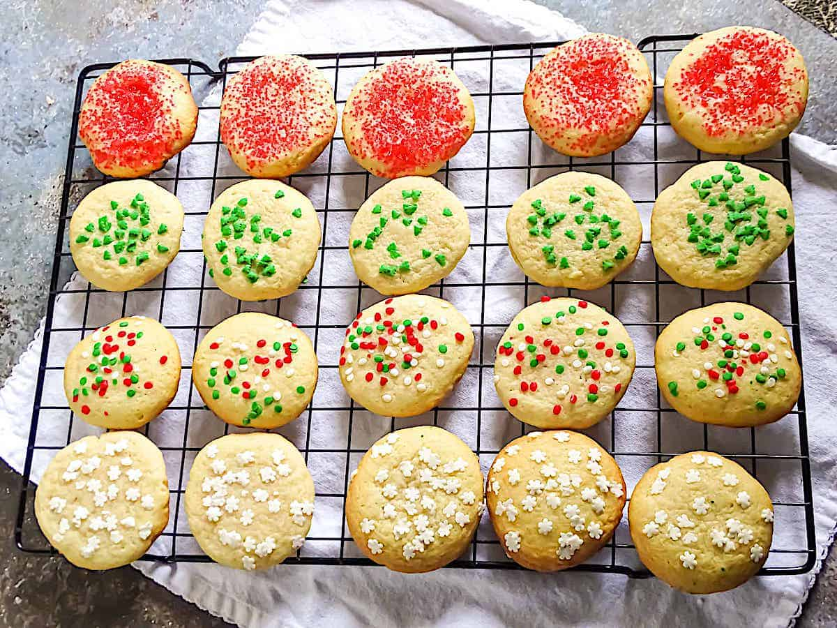Soft sugar cookies for Christmas decorated with festive sprinkles on a wire cooling rack