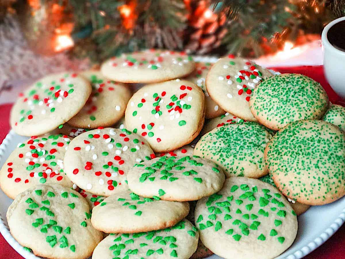 soft Christmas sugar cookies decorated with red and green sprinkles on a white plate