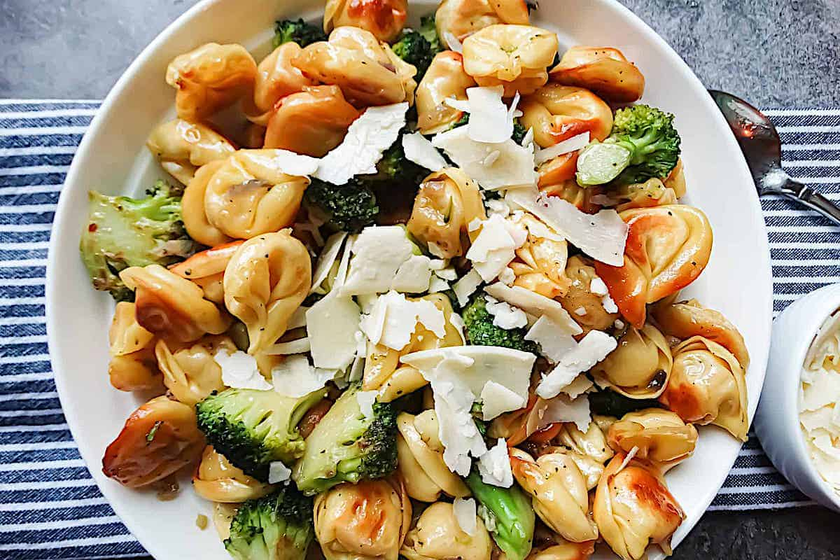 fried tortellini and broccoli in a white plate topped with parmesan cheese