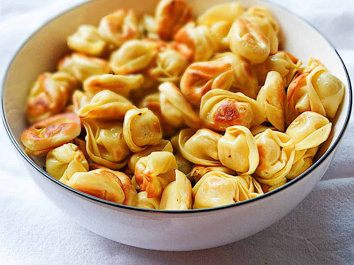 golden brown pan fried tortellini in a white bowl