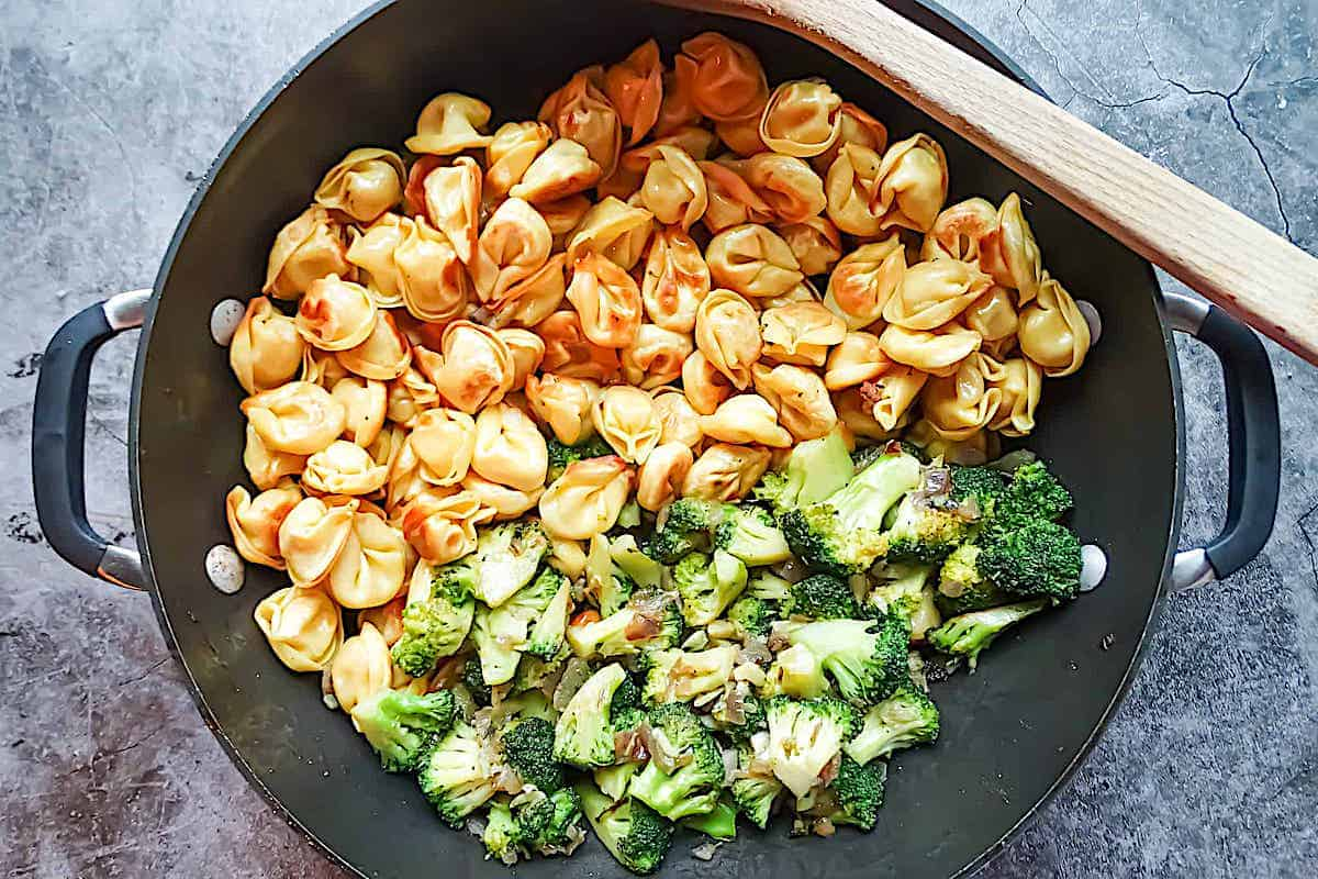 broccoli and tortellini separated in a wok
