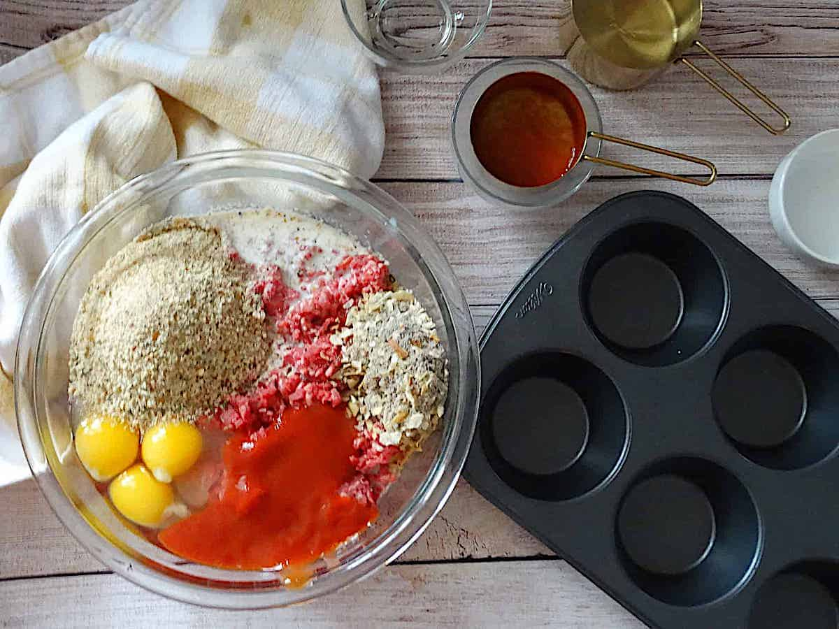 muffin tin meatloaf ingredients in a mixing bowl, next to a muffin tin
