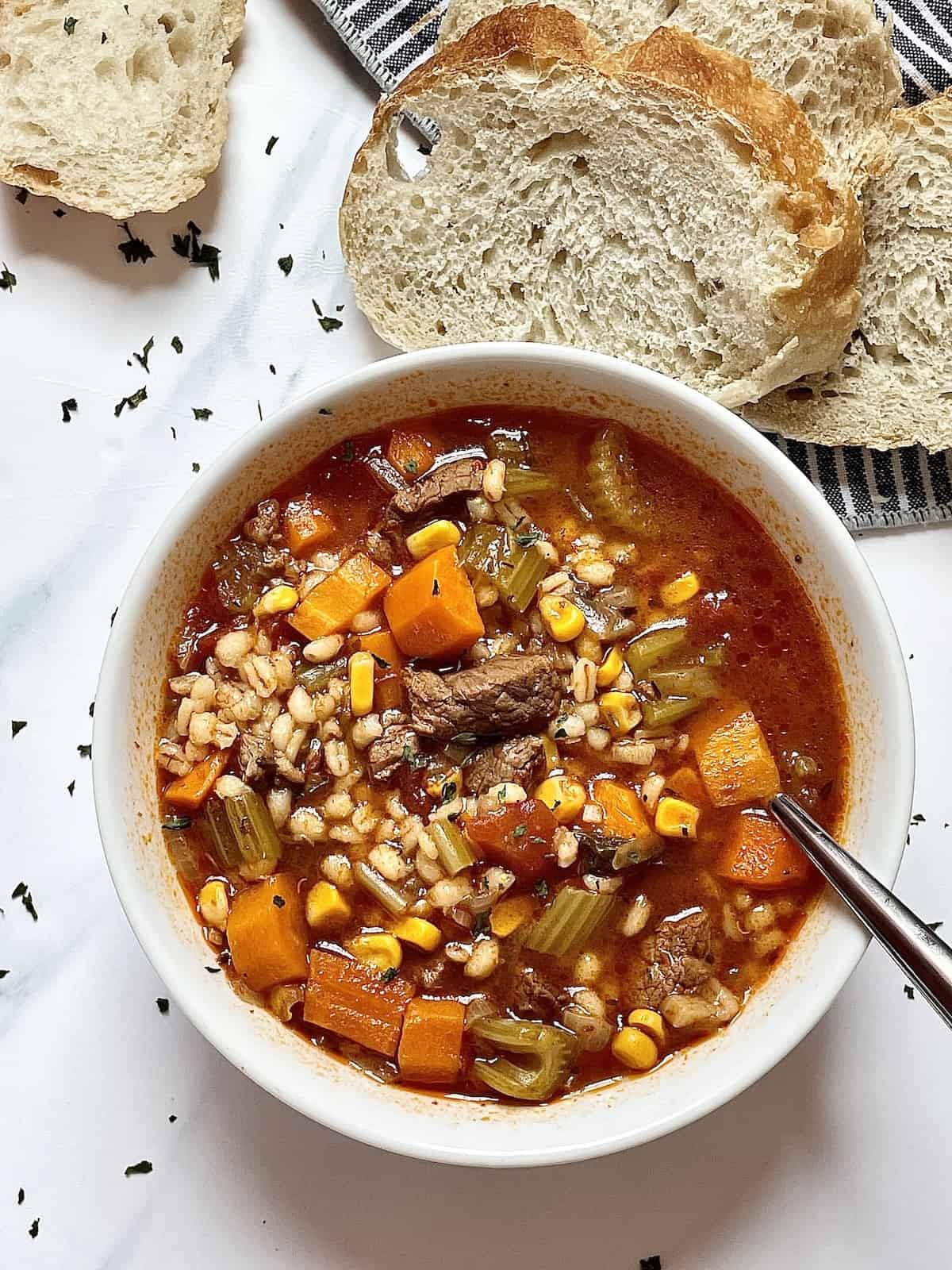instant pot beef and barley soup in a white bowl on a white background, surrounded by sliced bread and parsley flakes