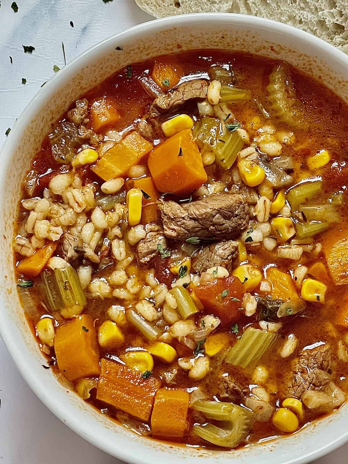 instant pot beef and barley soup in a white bowl
