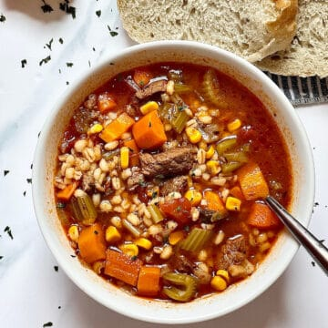 beef barley soup in a white bowl with a white background, with sliced bread and scattered parsley