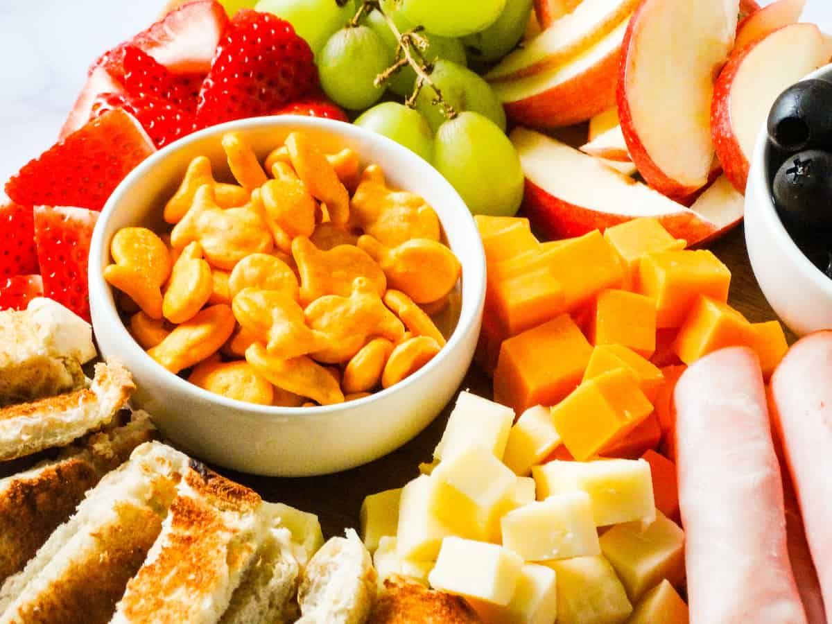 part of a kid-friendly charcuterie board, focused on gold fish, cheese, grapes and apples