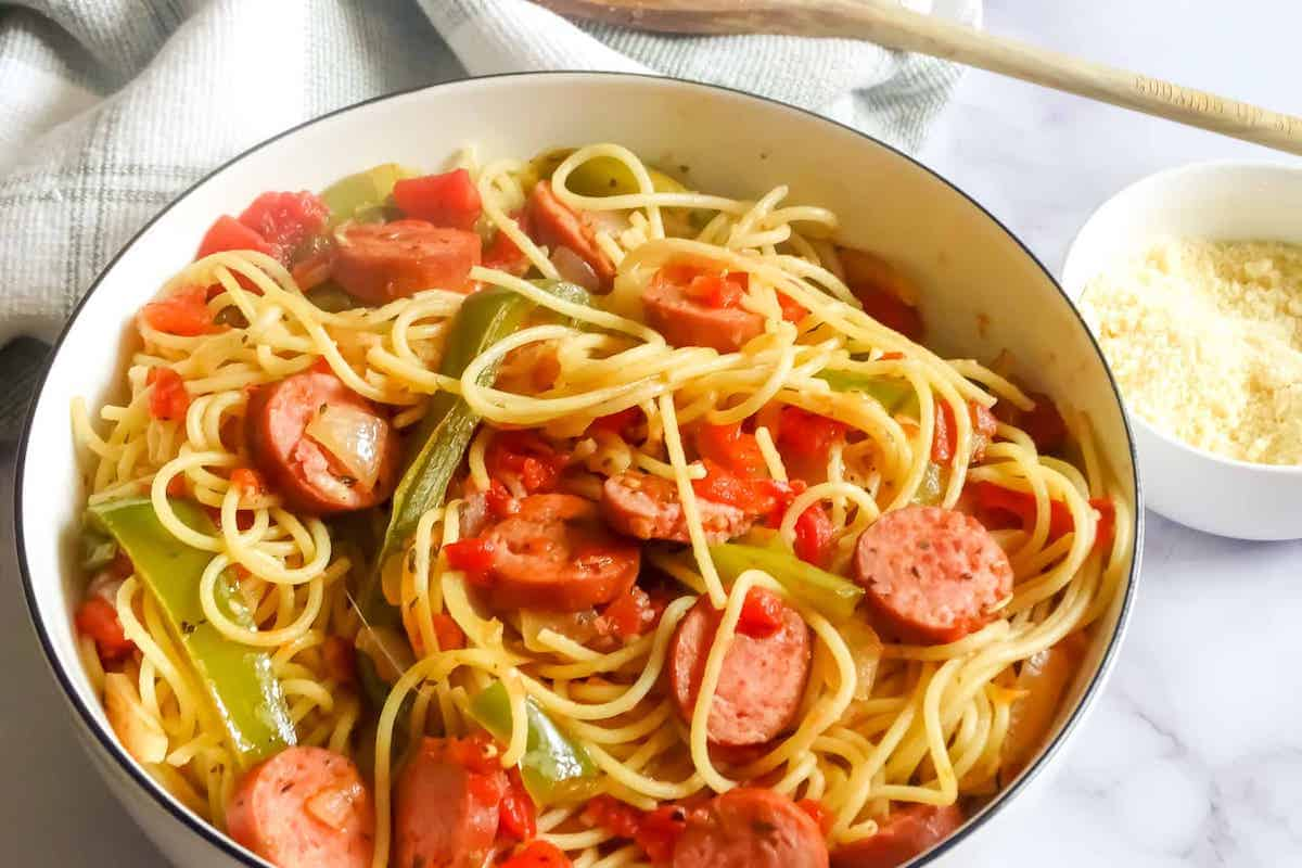 kielbasa and pepper pasta in a serving bowl with parmesan cheese