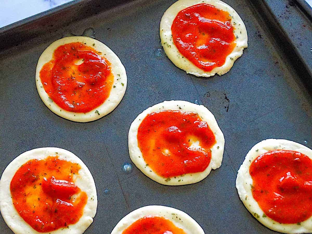 mini pizza dough topped with sauce