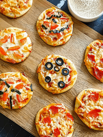 mini party pizza on a cutting board with various toppings