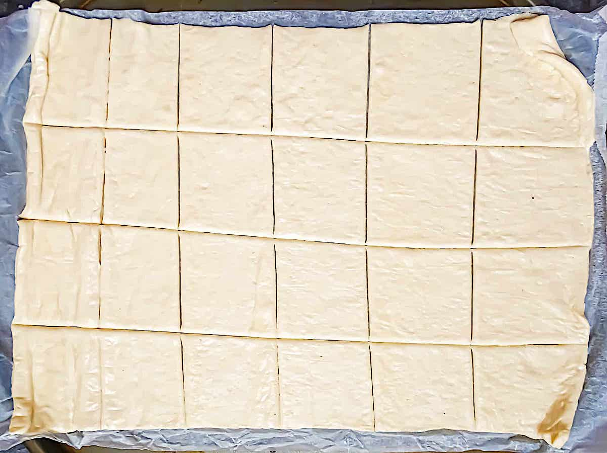 pizza dough spread onto a baking sheet and cut into 24 small squares