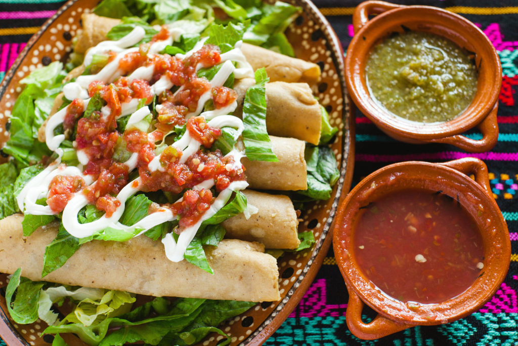 baked avocado chicken taquitos drizzled with cilantro lime crema and served with salsa
