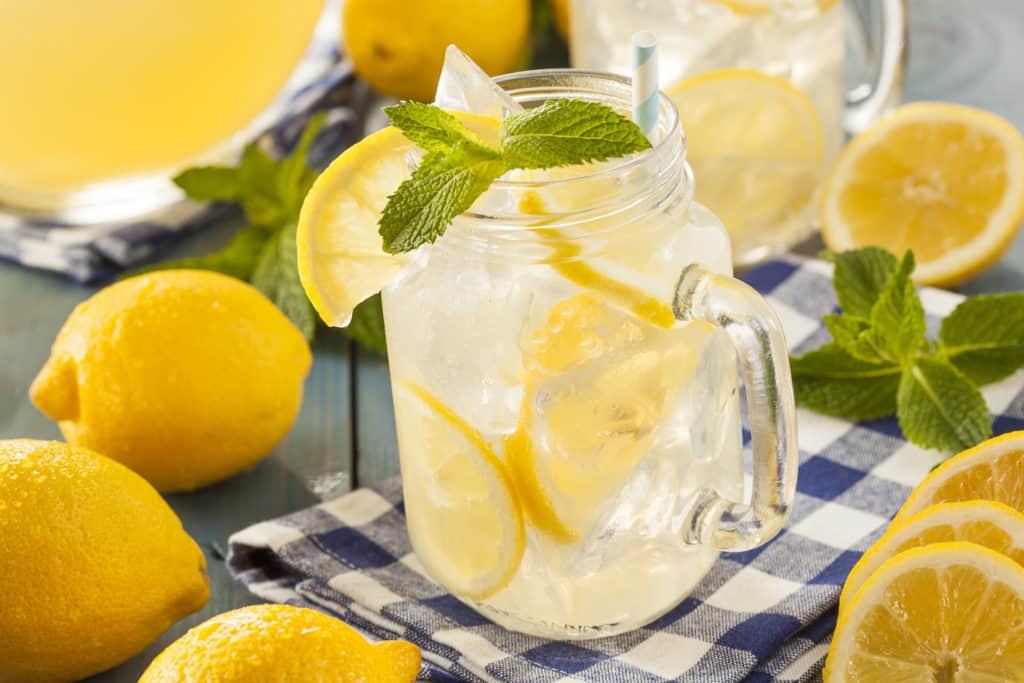 easy homemade lemonade recipe in a mason jar surrounded by lemons