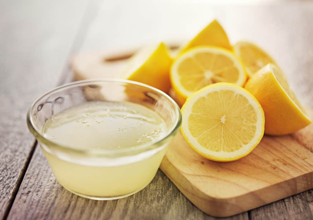 freshly squeezed lemon juice in small bowl surrounded by sliced lemons