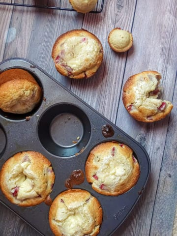 strawberry cheesecake muffins in a jumbo muffin win with wooden background