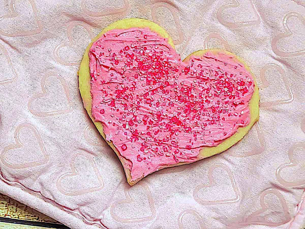 heart shaped cookie topped with icing and sprinkles