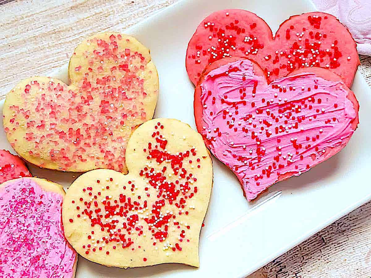 Valentine's heart shaped cookies topped with sprinkles and icing on a white plate