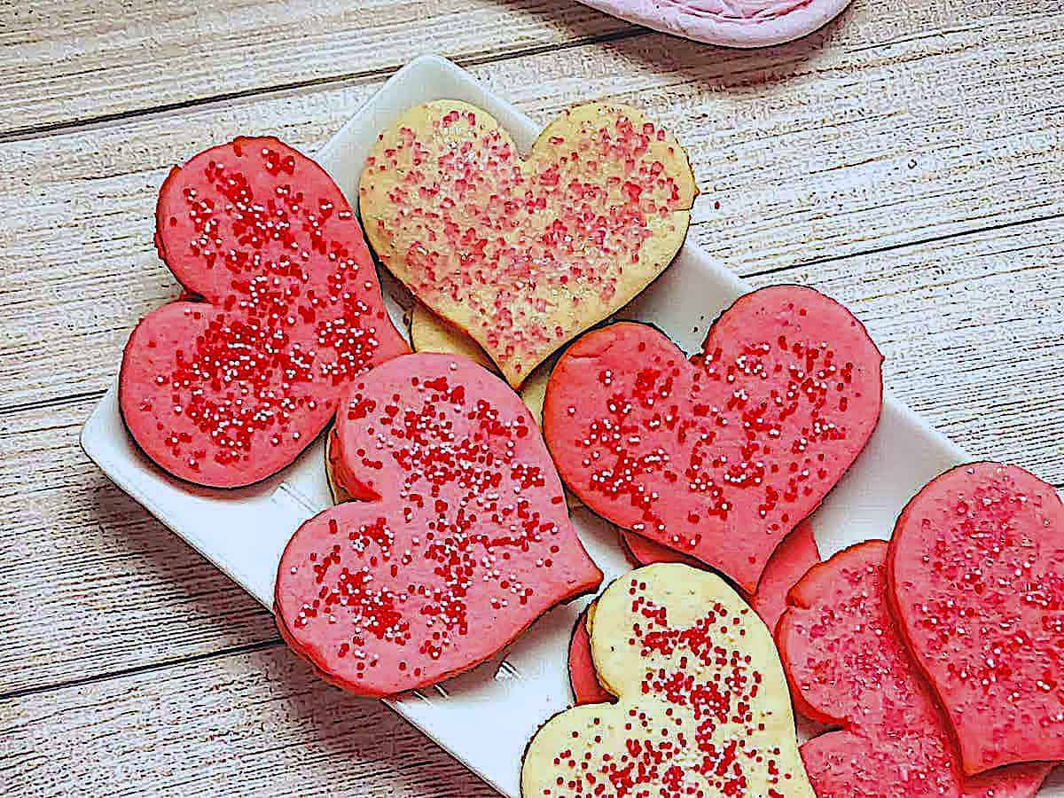 Valentine's Butter Cookies dyed pink and in the shape of hearts on a white plate
