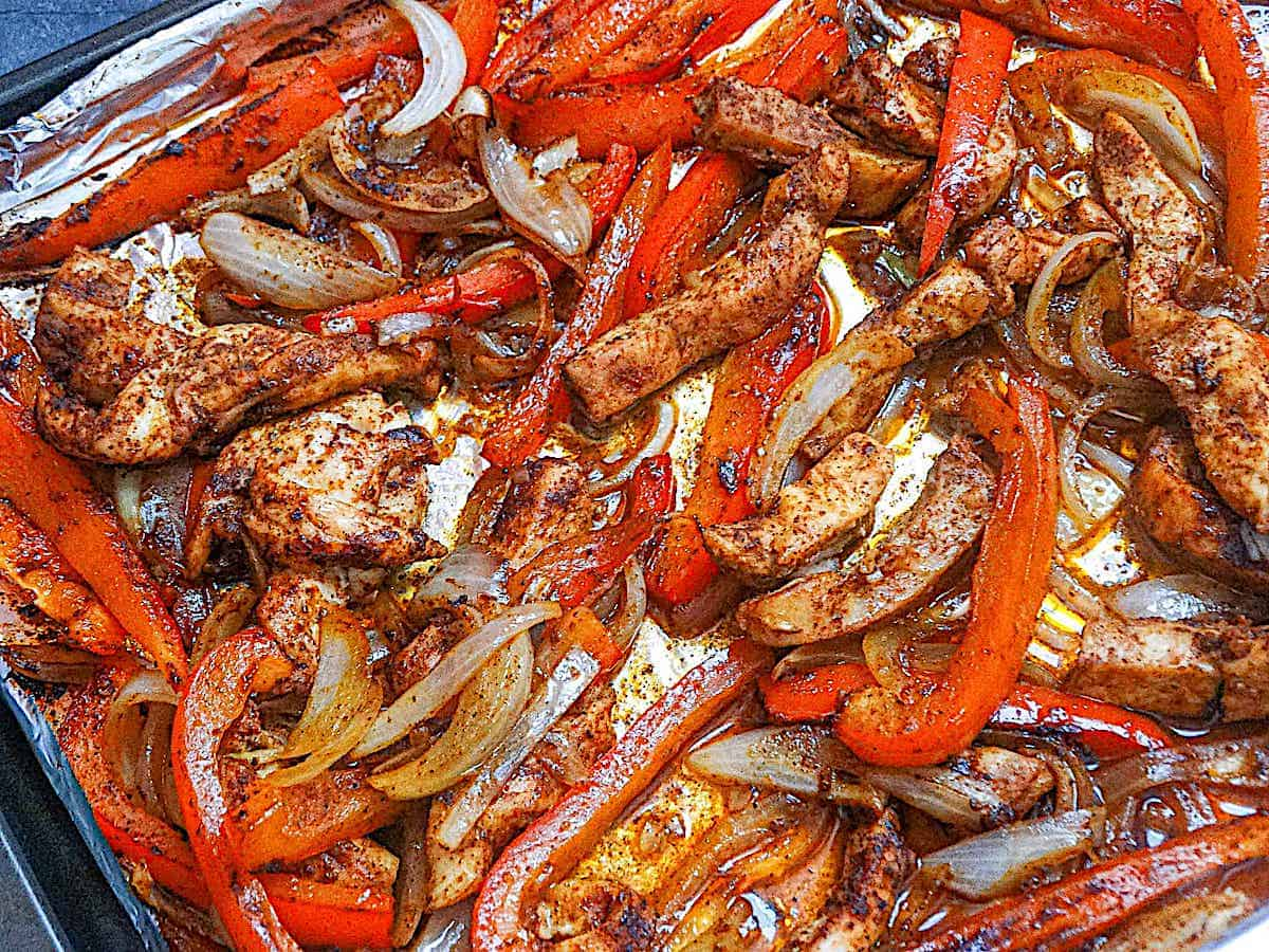 baked chicken fajitas with peppers and onions on a sheet pan