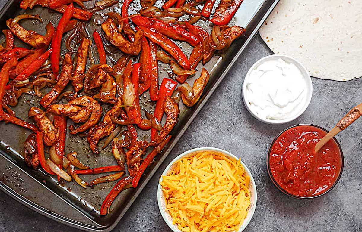 baked fajitas on a sheet pan served with cheddar cheese and sour cream