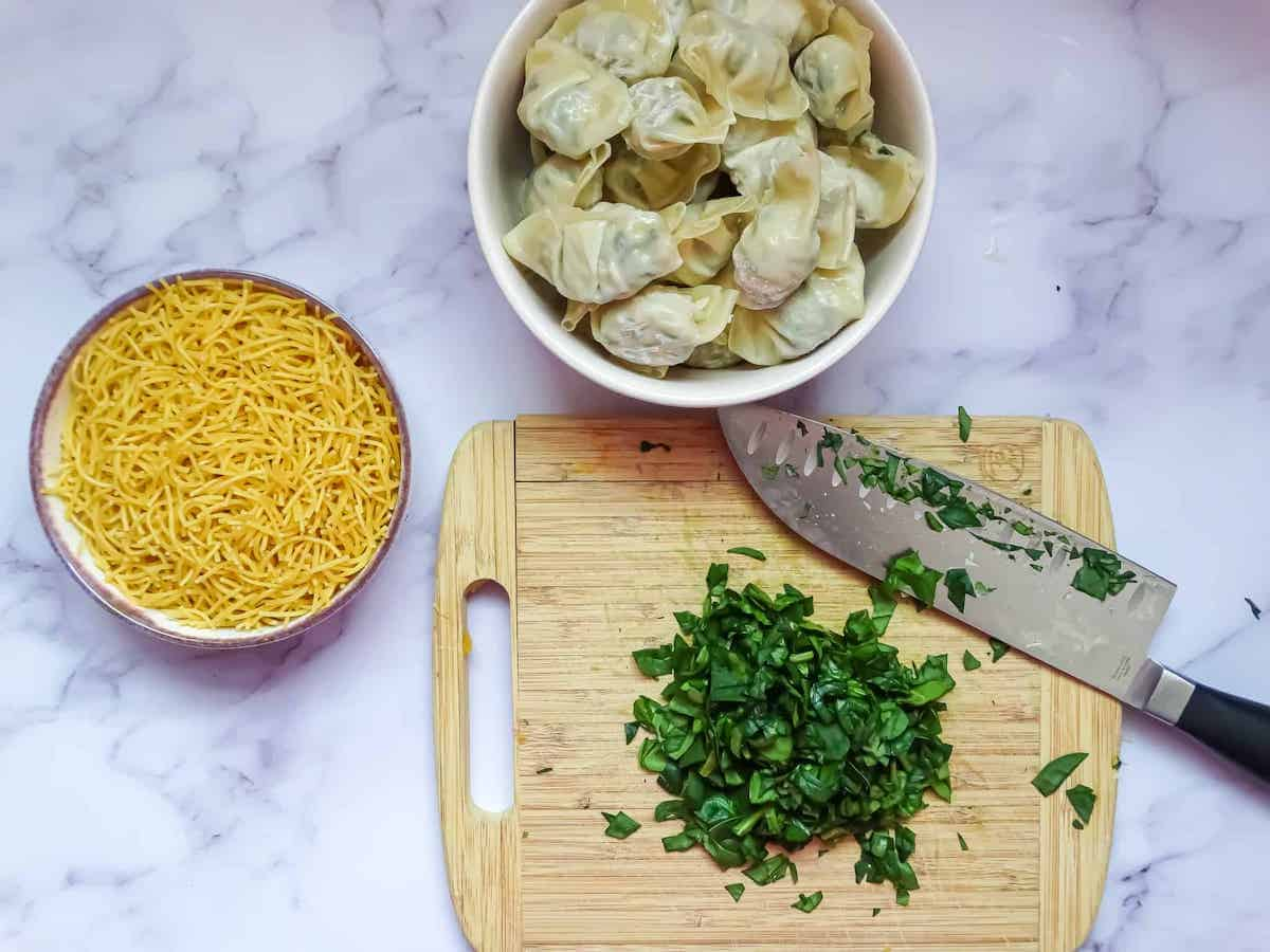 spinach, dumplings, and noodles on a cutting board