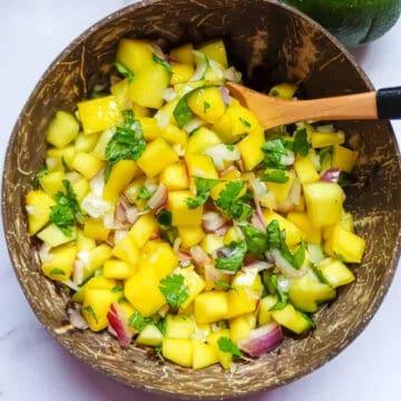 mango pico de gallo in a coconut bowl