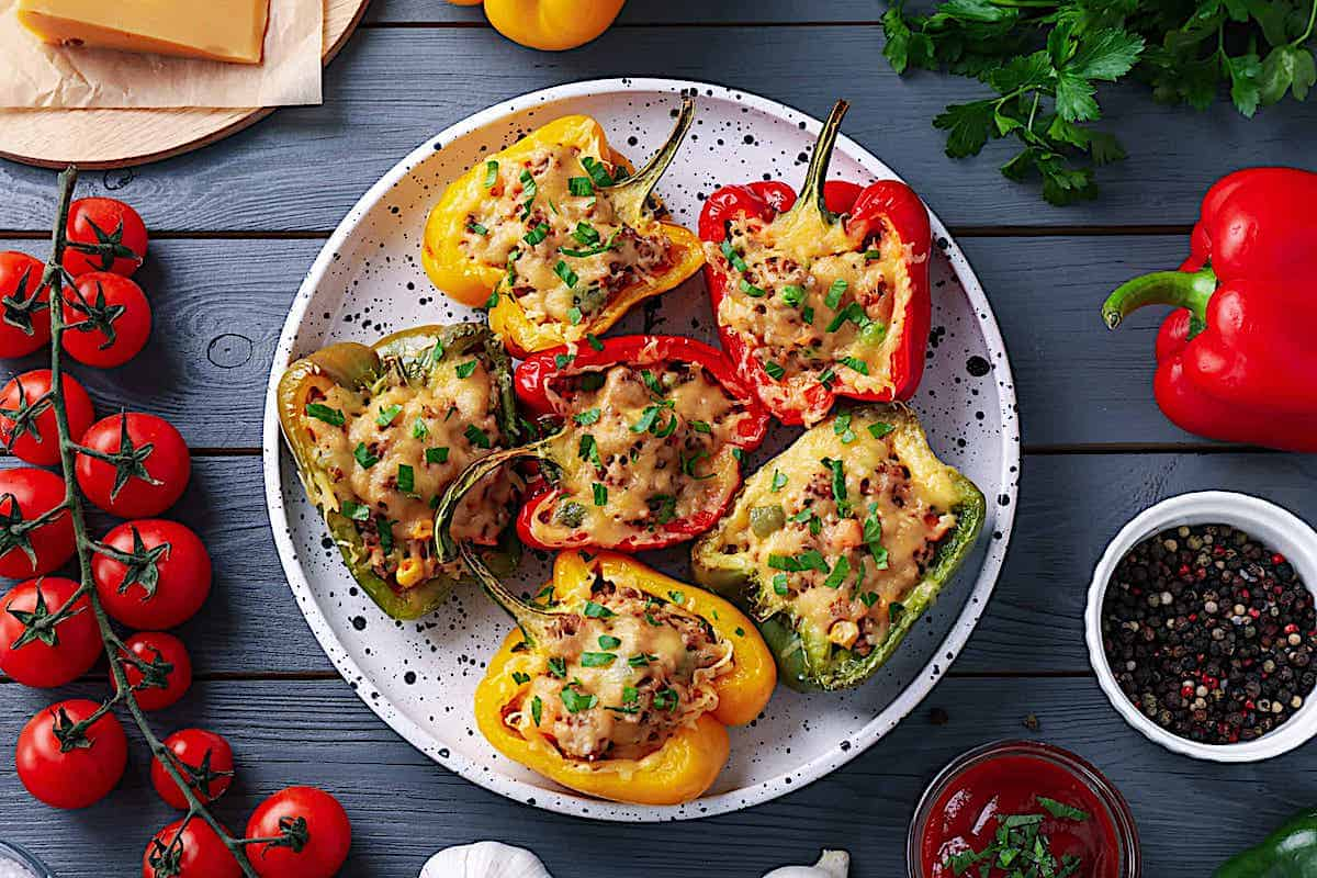 large bell peppers stuffed with meat and cheese on a white plate