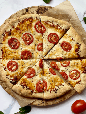white pizza with tomato and basil on a white surface