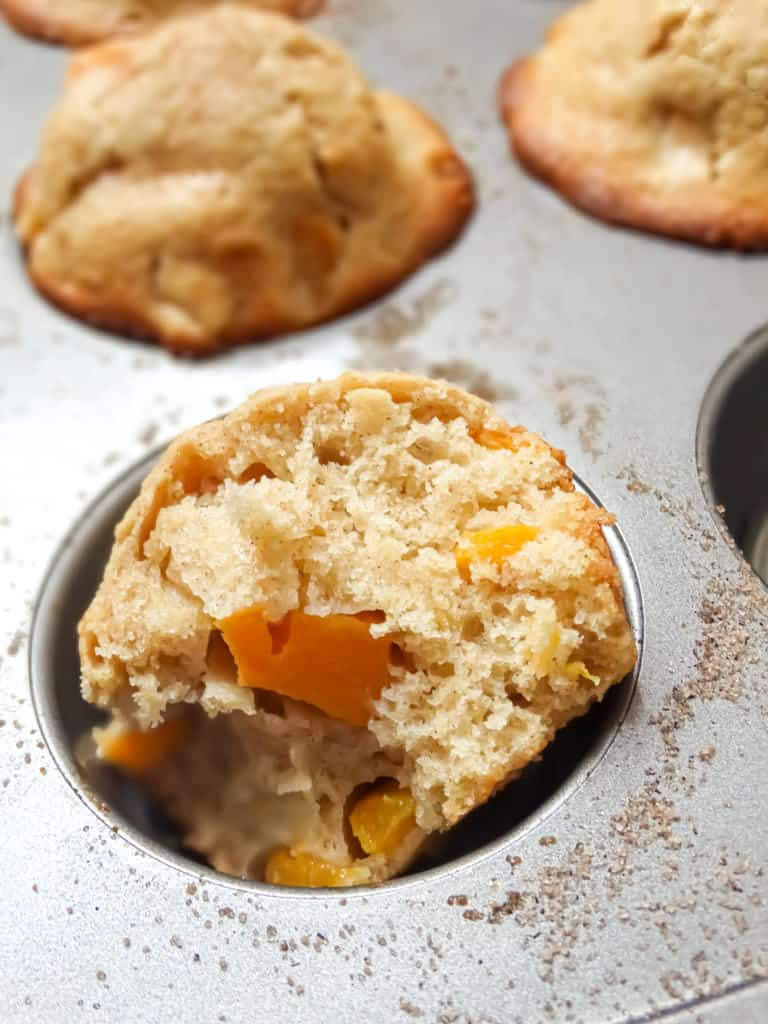 peach muffins in a muffin tin sprinkled with cinnamon sugar