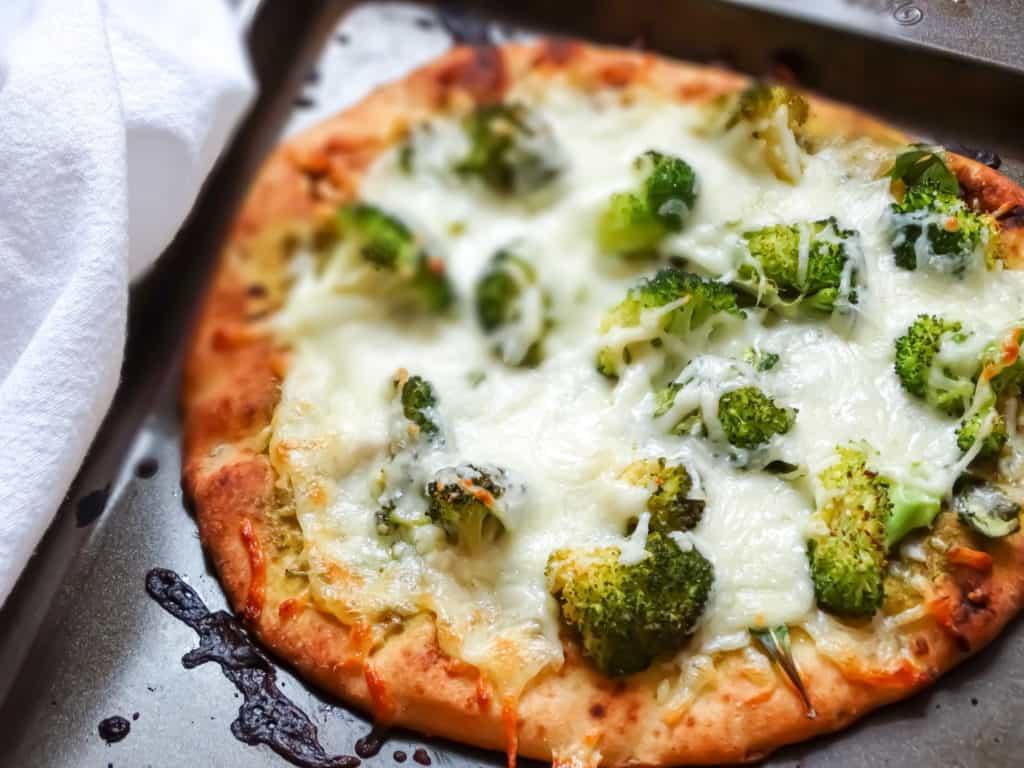 green pizza with broccoli and mozzarella