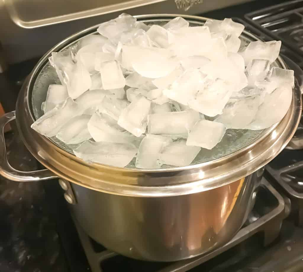 ice in a lid on top of boiling water to make distilled water
