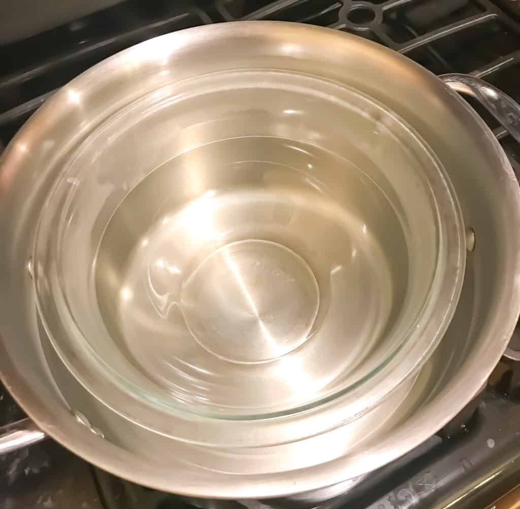 a glass bowl in a large pot of water