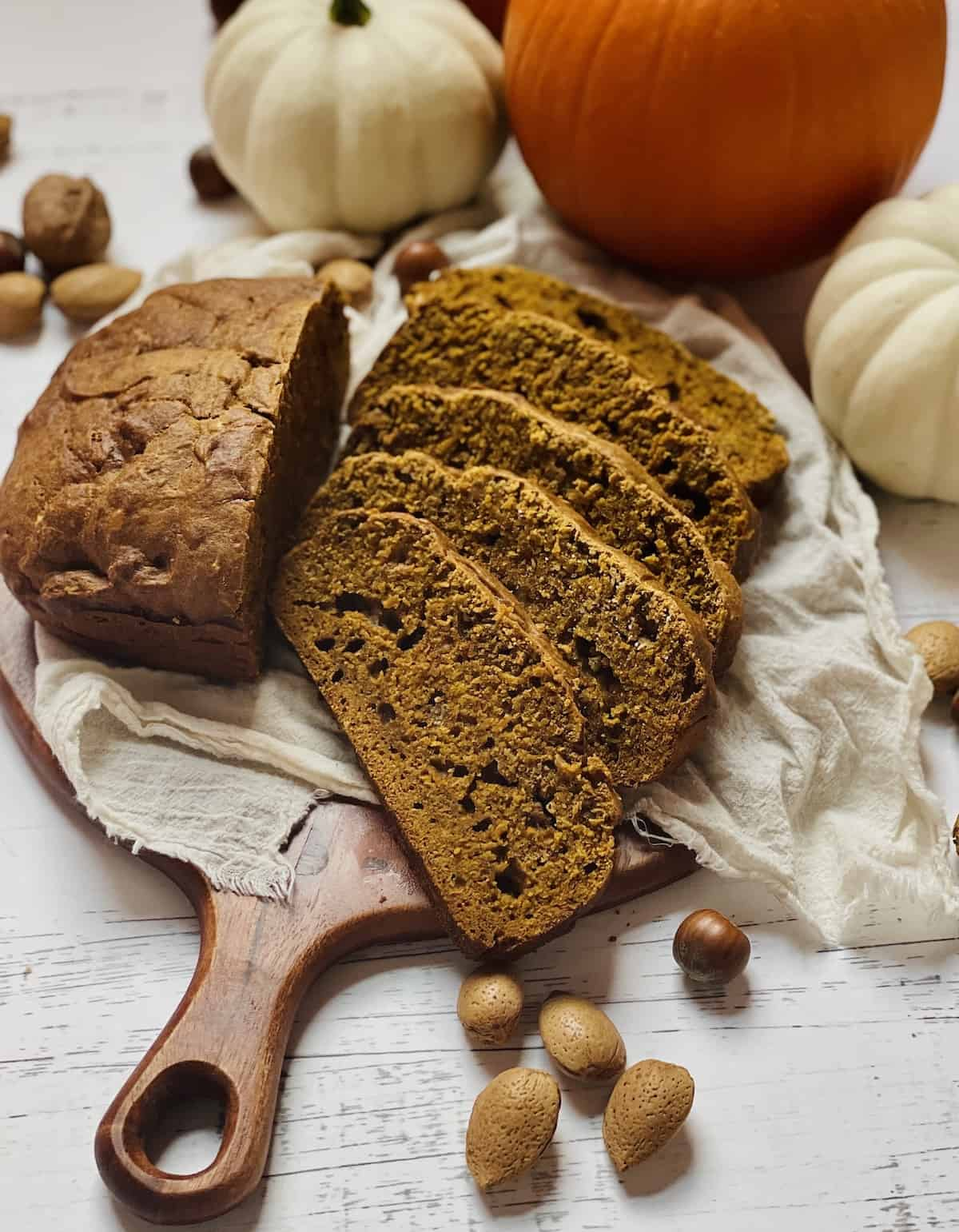 bread machine pumpkin bread sliced on a cutting board surrounded by nuts and pumpkins